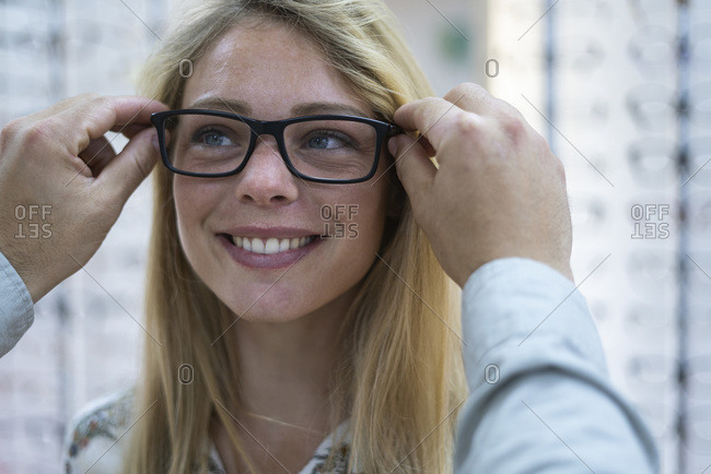 Close-up of salesperson helping customer to wear eyeglasses in store