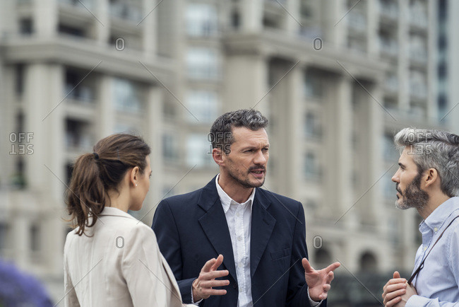 Businesspeople talking together in a city