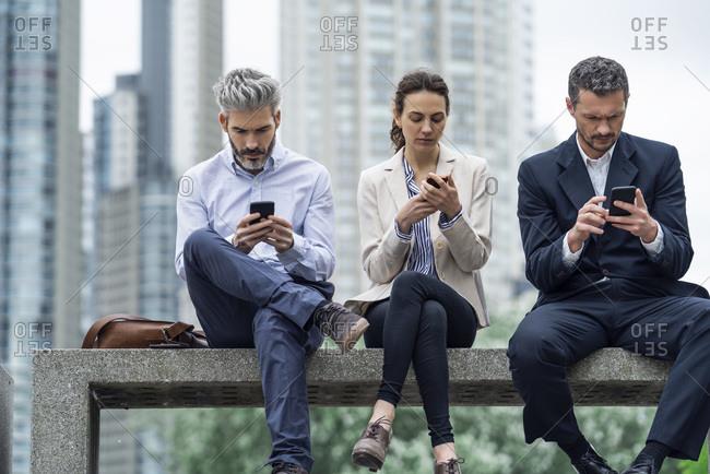Business people using smartphones in public park