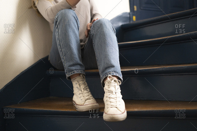 Low section of young woman sitting on steps