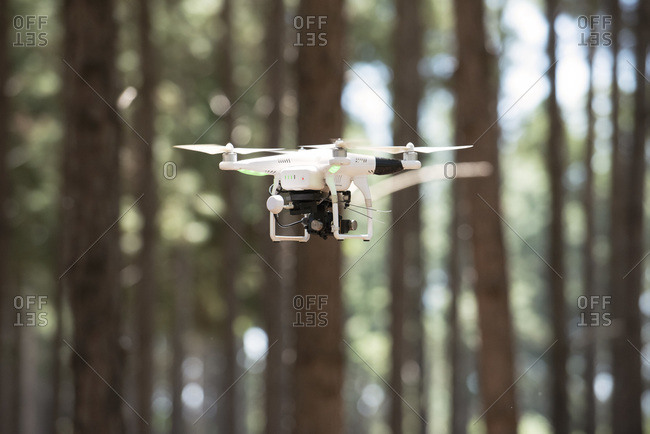 White drone flying in forest