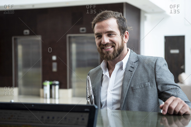 Businessman standing at hotel reception counter