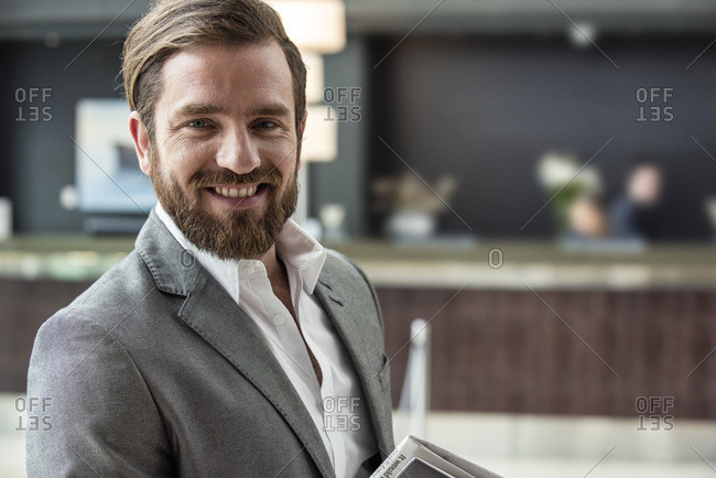Smiling businessman standing in hotel lobby