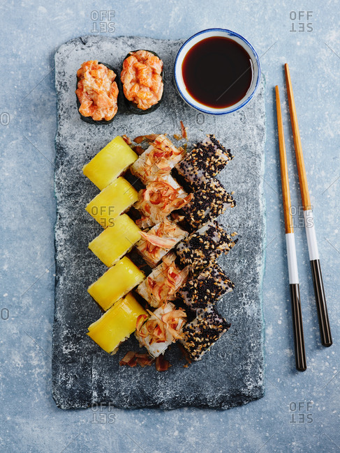 Assorted Japanese maki sushi rolls with soy sauce on stone plating board with chopsticks