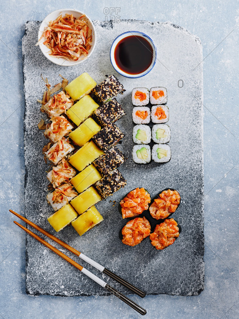 Beautifully plated various sushi and maki rolls served with soy sauce and tuna flakes on light gray background
