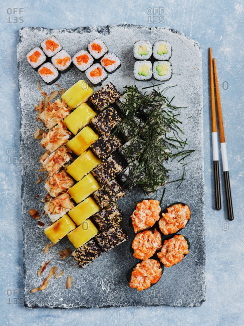 Colorful assortment of different maki sushi rolls served on stone board with chopsticks