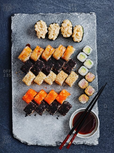 Top view of beautifully plated assorted Japanese sushi rolls with soy sauce and chopsticks on stone serving board