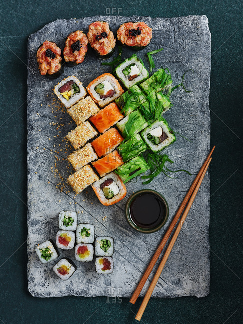 Bright and beautifully plated assorted sushi rolls on stone serving board with chopsticks and soy sauce