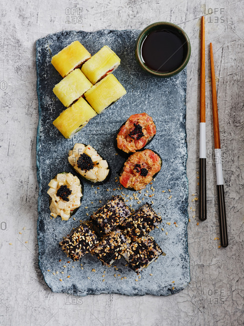 Assorted maki and gunkan sushi rolls with chopsticks and soy sauce