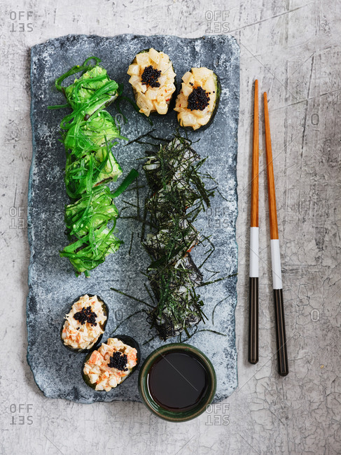 Appetizing Japanese maki sushi set on stone serving board with chopsticks and soy sauce