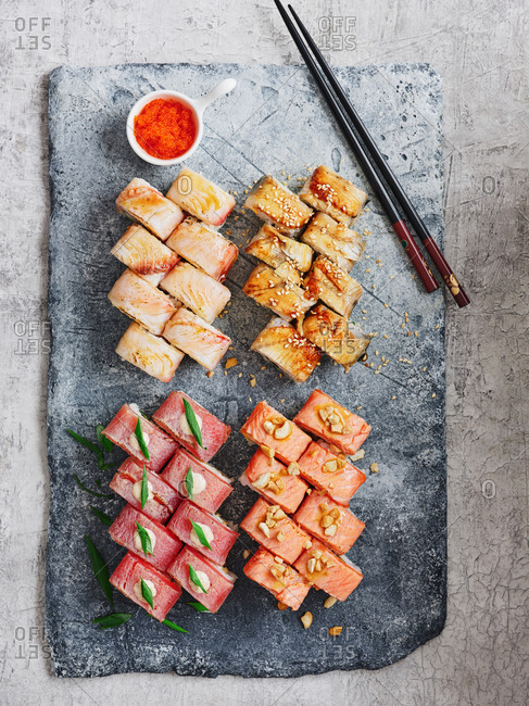 Bright and beautifully plated assorted maki sushi rolls with red flying fish roe on stone serving board