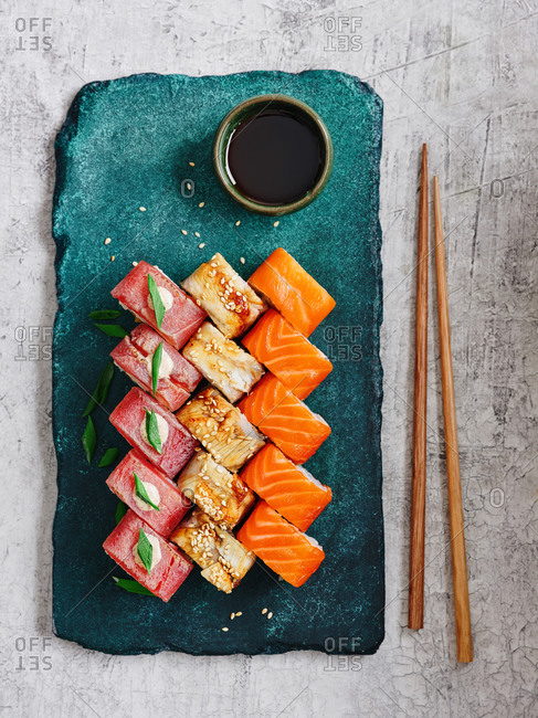 Japanese maki sushi rolls with salmon, tuna and smoked eel with chopsticks served on turquoise stone serving board on light background