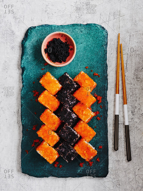 Selection of maki sushi with red an black flying fish roe on turquoise stone serving board on light background