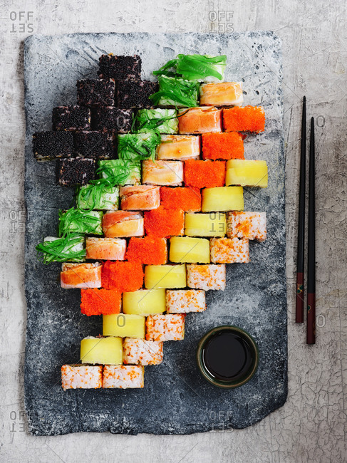 Big and colorful set of Japanese maki sushi rolls with various seafood on stone serving board