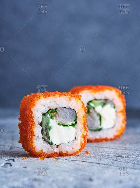 Macro view of maki sushi roll with white fish fillet, cream cheese and red tobiko caviar