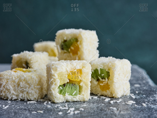 Close up view of sweet sushi rolls with shredded coconut and tropical fruits (mango, pineapple and kiwi fruit)