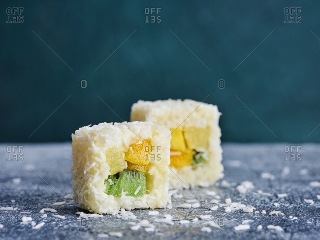 Close up of dessert sushi rolls with fresh tropical fruits and coconut