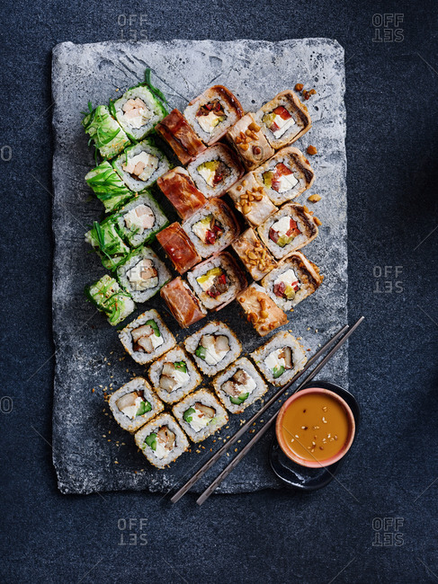 Contemporary plated maki sushi set with spicy peanut sauce served on beautiful stone plating board