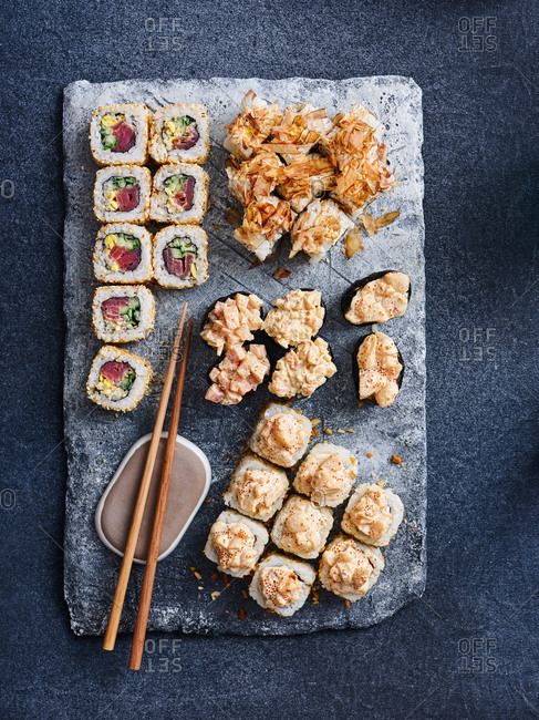Selection of Japanese appetizing gunkan and maki rolls with fresh and flaked tuna on dark background