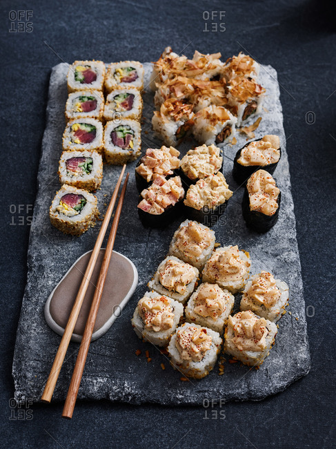 Close up view of beautifully plated gunkan and maki sushi set on stone serving board on dark background