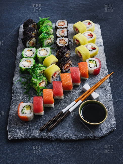Close up view of colorful sushi set with assorted fish and seafood on dark background