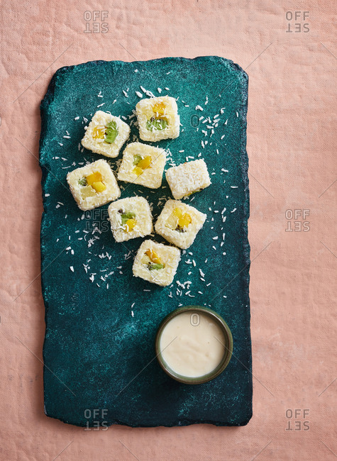 Sweet sushi rolls with coconut flakes, kiwi fruit, mango and orange on turquoise stone serving board on pink background