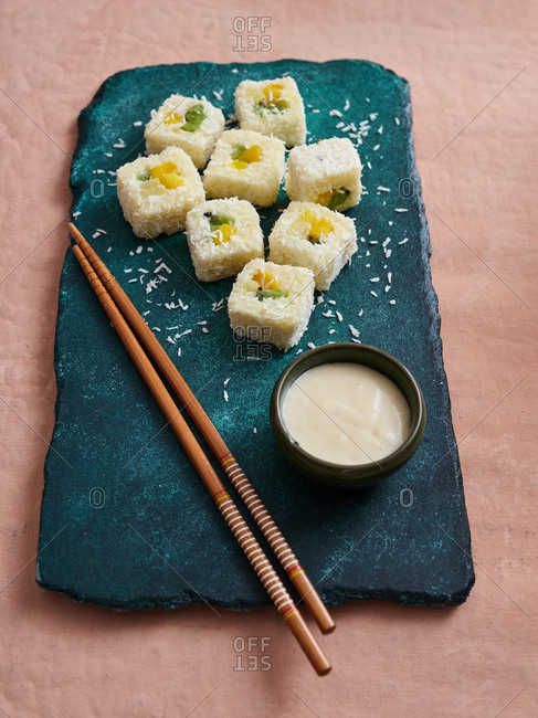 Serving of sweet sushi rolls with fruits and dipping sauce on stone board with chopsticks