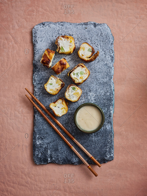 Top angle view of sweet dessert sushi rolls with tropical fruits and delicious coconut dipping sauce on pink background