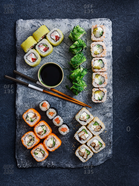 Beautifully plated assorted sushi rolls with chopsticks and soy sauce on dark background