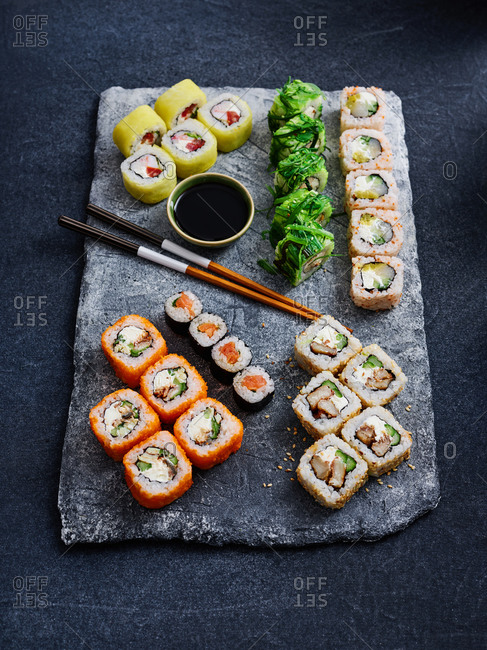 Close up view of colorful sushi set with salmon, tuna, eel and shrimps on stone serving board