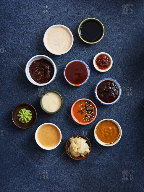Various sauces and ingredients for oriental and asian cooking on dark textile background