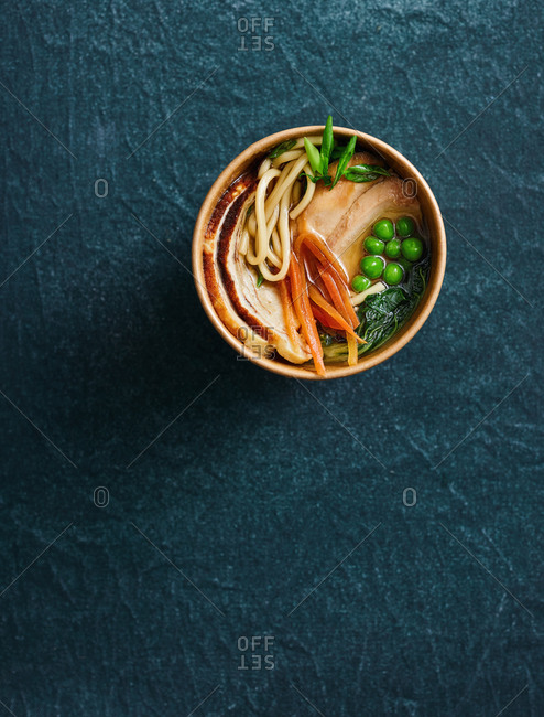 Top view of take away pork ramen soup with peas, carrot and noodles on dark background