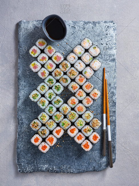 Beautifully plated big maki sushi set with various seafood fillings served on stone board with chopsticks and soy sauce