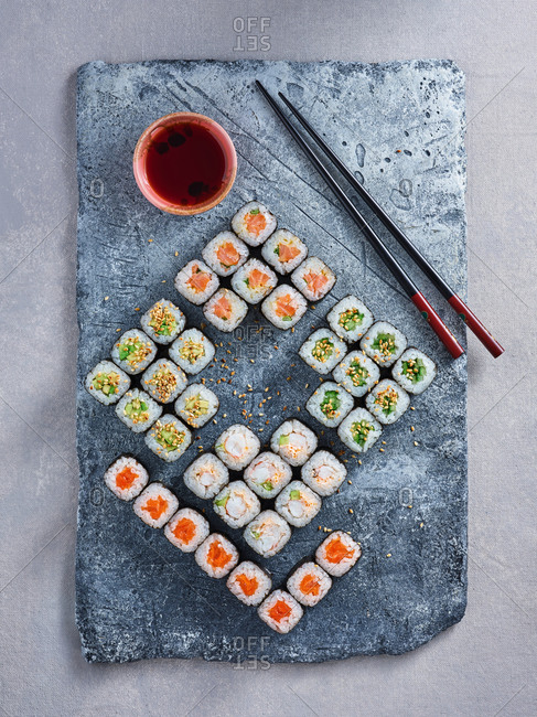 Assortment of Japanese appetizing sushi rolls on stone serving platter on light background