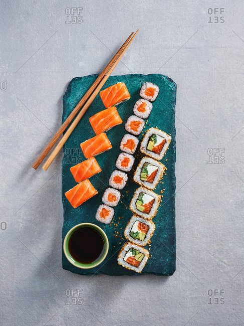 Assorted fusion sushi rolls with salmon, cream cheese and avocado on turquoise stone serving board on light background