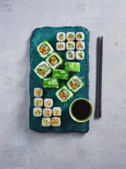 Spicy wakame seaweed sushi rolls  with vegetables on turquoise stone serving board on light background