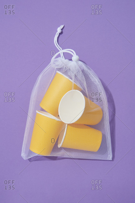 Transparent reusable shopping bag with blank yellow cups on a purple background with shadow, copy space . Flat lay. Eco friendly concept.