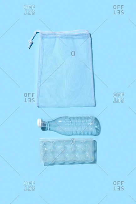 Composition from reusable shopping bag, plastic eggs box and bottle on a light blue background with shadows, copy space. Flat lay. Eco friendly concept.