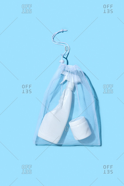 Reusable shopping bag with plastic cream box and spray bottle on a light blue background with shadows, copy space. Flat lay. Eco friendly concept.