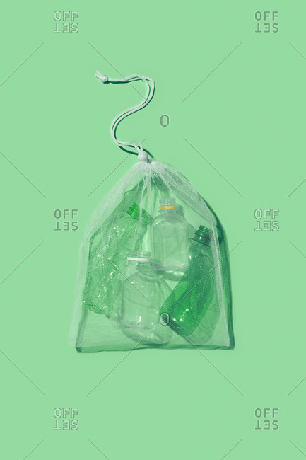 Plastic empty bottles different shapes in a reusable bag as a used garbage on a light green background with shadow, copy space. Waste sorting concept.