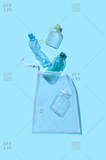 Blank plastic bottles different size and shapes fall into refillable package as a used garbage on a light blue background with shadow, copy space. Waste sorting concept.
