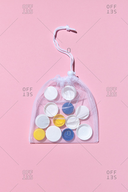 Plastic used colorful lids from different bottles in a reusable bag on a light pink background with shadow, copy space. Waste sorting concept.