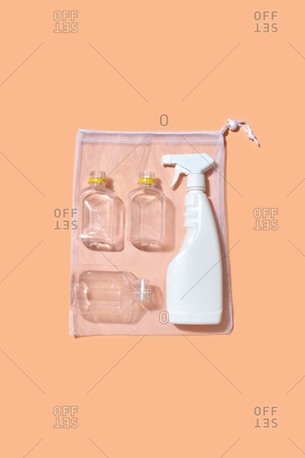 Plastic mock-up bottles, cans and spray on a refillable package for multiuse on a light peach color background with shadow, copy space. Eco friendly concept.