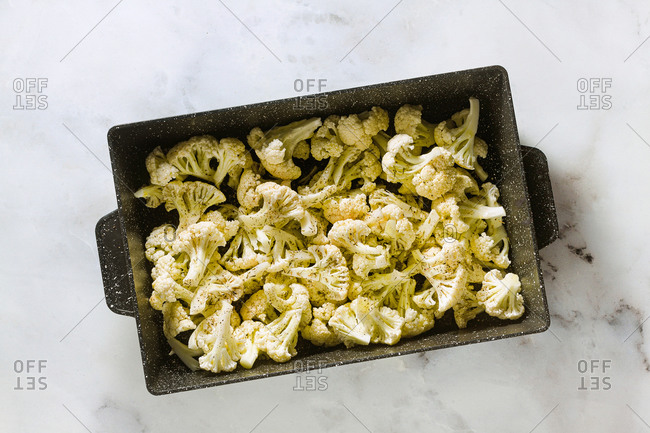 Slices of cauliflower in a baking tray with olive oil, aromatic herbs and spices, ready for baking on the marble table, copy space.