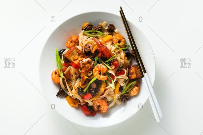 Classic pad thai with shrimp, vegetables and wheat pasta with a plate on a white table with chopsticks, copy space. Top view.