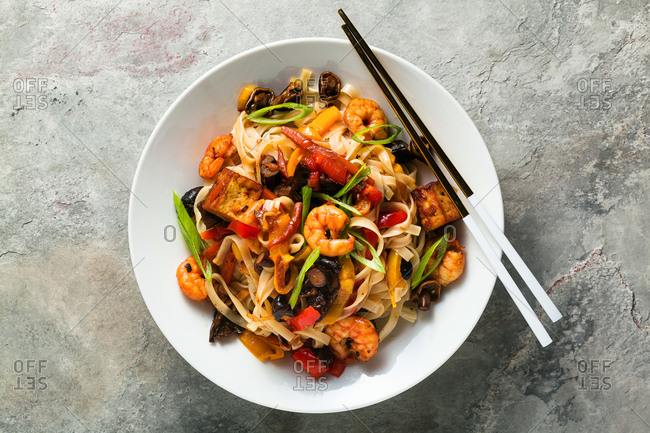 Classic pad thai with shrimp, fresh vegetables and wheat pasta with a plate on a table with chopsticks on gray stone background, copy space. Top view.