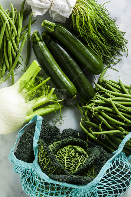 Fresh organic green italian vegetables on a marble table and Cotton Mesh Net String Shopping Bag. Zucchini, green beans, fennel, savoy cabbage and Salsola soda.