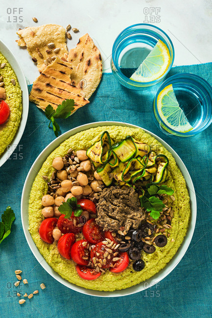 Homemade green hummus with fresh peas and stuffed with olive pate, grilled zucchini, olives and cherry tomato with toasted sunflower seeds and flat bread on the table covered blue cloth, copy space.