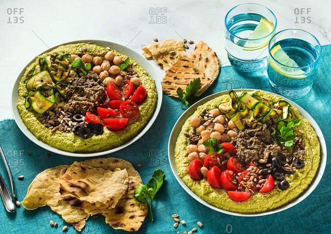 Home cooked hummus with fresh peas and stuffed with olive pate, grilled zucchini, olives and cherry tomato with toasted sunflower seeds and flat bread on the table covered blue textile, copy space.