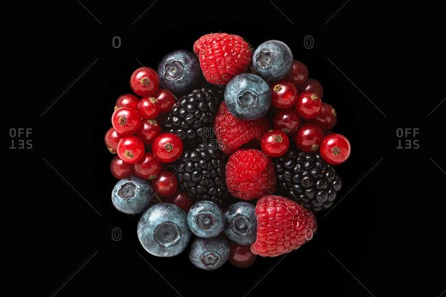 Freshly picked natural organic berries in the shape of circle isolated on a black background. Vegetarian concept.